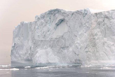 Photo pour Arctique Groenland d'Icebergs dans la mer de l'Arctique. Vous pouvez facilement voir que cet iceberg est au-dessus de la surface de l'eau et sous la surface de l'eau. Parfois incroyable que 90 % de l'iceberg est sous l'eau - image libre de droit