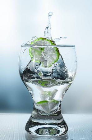 Splash water in a glass with a lime and a bottle in beige tones