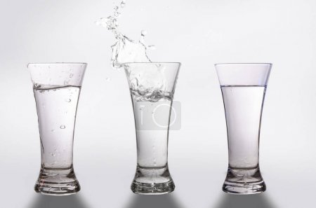 three glasses and a splash of water on a gray background