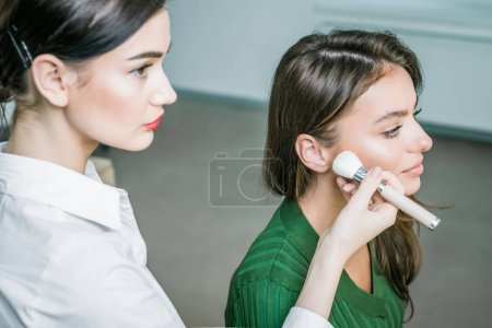 Photo for Closeup portrait of a woman applying dry cosmetic tonal foundation on the face using makeup brush. Makeup detail. - Royalty Free Image