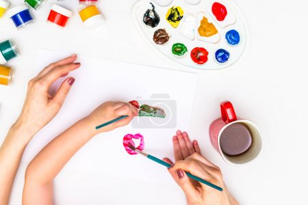 Photo for Top view childs hands draws a gouache on paper. Gouache and paper for painting and child drawing. - Royalty Free Image