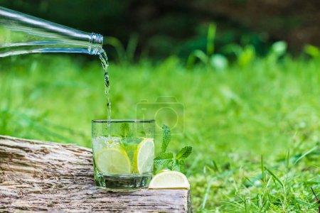 Photo pour Verser l'eau d'une bouteille dans un verre extérieur - image libre de droit