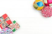 Gift boxes and New Year ornaments and toys on white wooden background