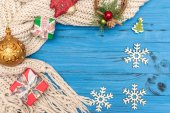 Gift boxes, decorative wooden snowflakes and New Year ornaments and toys on blue wooden background