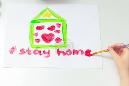 Photo for Top view of children hand drawing Stay Home words under painted house with hearts by brush with watercolors on white paper at home. - Royalty Free Image
