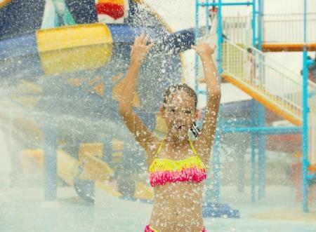 Cheerful preteen girl splashing water towards the camera. Blurre