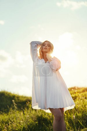 Photo for Girl in a long white dress dancing in the field. Blonde woman in the sun in a light dress. Girl resting and dreaming, perfect summer makeup on her face - Royalty Free Image