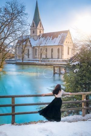 Frau meditiert am blauen Seeufer