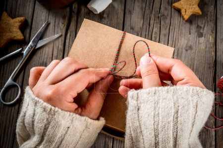 Photo for Preparation for the autumn and winter holidays. The person packs the cookies as a gift in a craft box, Christmas ribbon, hands in the frame. Rustic old table, top view copy space - Royalty Free Image