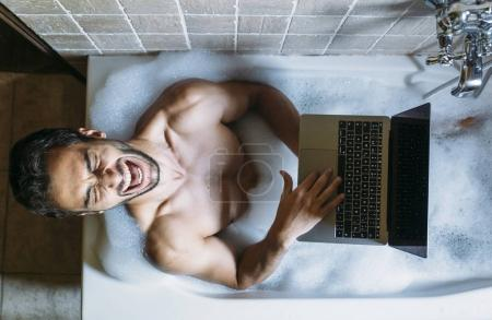 Photo for Naked guy in bathroom with laptop - Royalty Free Image