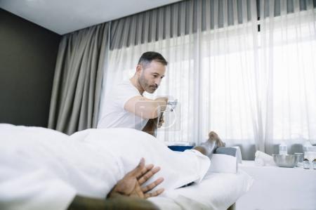 Photo pour Le physiothérapeute traitant un homme utilisant un équipement pour la radiothérapie - image libre de droit