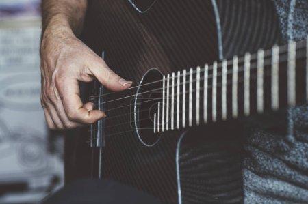 Photo pour Homme âgé jouant de la guitare en fibre de carbone - image libre de droit