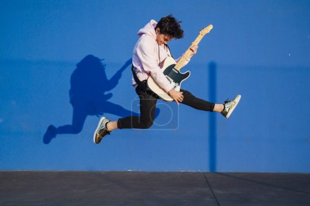 Photo for Young man jumping with electric guitar on blue background - Royalty Free Image