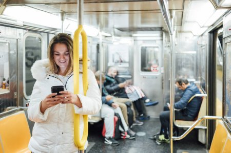 Photo for Woman travel in subway with smartphone - Royalty Free Image