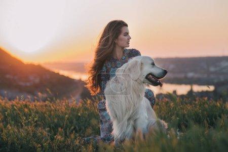 Woman  with her dog enjoying sunset.