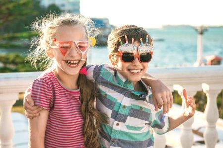 Photo pour Portrait de deux enfants préadolescents - garçon et fille (9-10 ans) vêtus de lunettes de fête amusantes et célébrations d'anniversaire . - image libre de droit