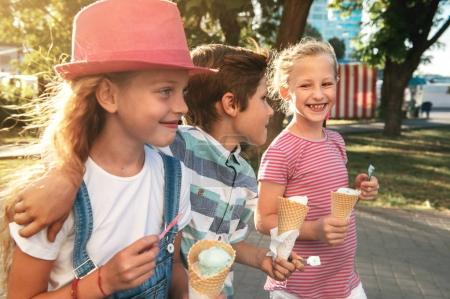 Close-up portrait of three happy preteen children walking on the street, having fun and eating ice-cream