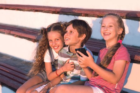 Portrait of group preteen children sitting on a bench and play on smartphones and having fun