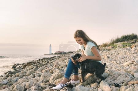 Beautiful teenage girl playing her pet dog at the beach on sea shore. Young woman walking with zwergschnauze.