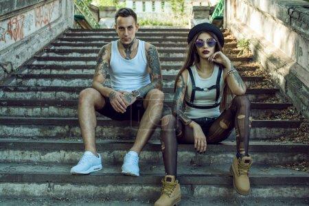 Jeune couple tatoué élégant en short noir assis sur les escaliers en ruine et regardant droit. Fille portant un chapeau, collants déchiré et lunettes de soleil en miroir