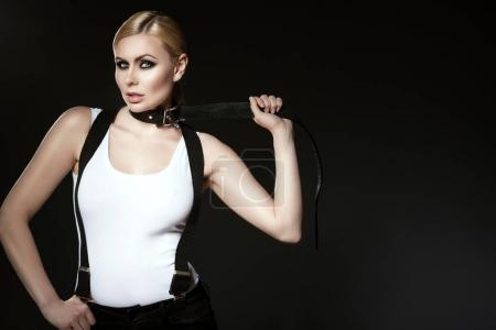 Portrait of chic blond model with pulled back hair and smoky eye make-up wearing white top with suspenders over her shoulders fastening a black leather belt on her neck. Copy space
