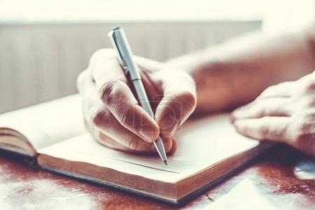 male hand is writing in  notepad