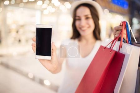 Woman with bags showing phone