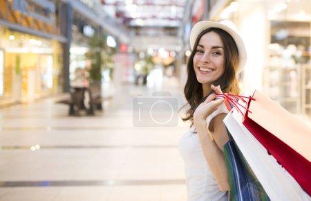 Photo pour Heureuse jeune femme souriante avec des sacs de shopping au centre commercial - image libre de droit