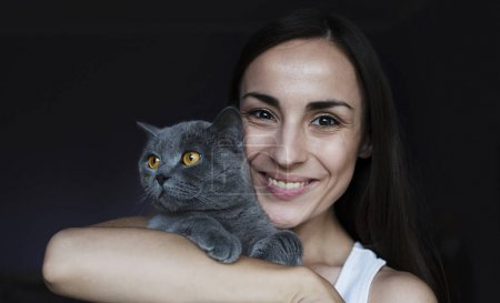 smiling woman holding grey cat