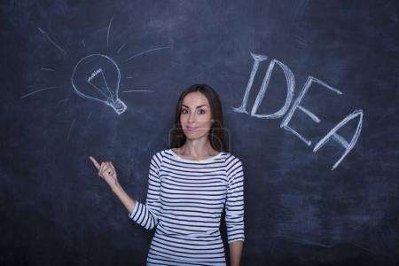 beautiful woman pointing on blackboard