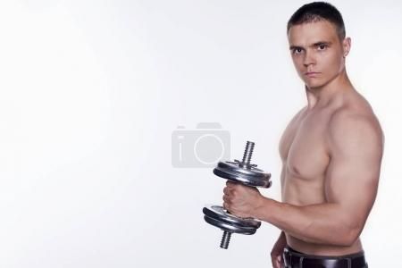 Portrait of young sporty man with dumbbell