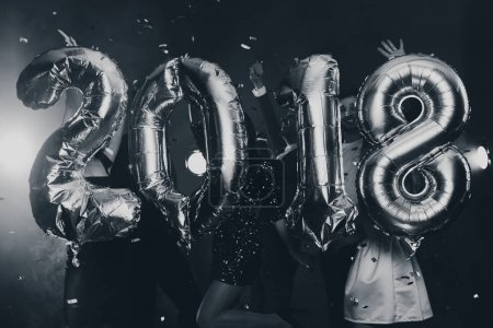 The composition of the golden balloons in the form of figures on a background of a dancing group of young people. The new year 2018. Festive New Year party or disco. Black and white photo
