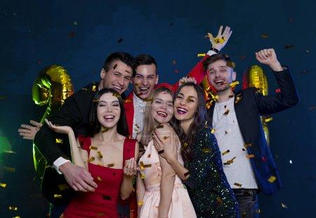 Nous vous souhaitons un joyeux Noël et une bonne année. Amis heureux et souriants au parti avec des confettis. Concept de personnes et les jours fériés. Célébration et fête. Nouvel an. Anniversaire