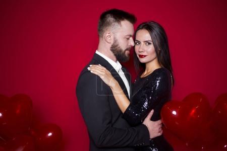 Foto de Te quiero. Suave elegante hermosa pareja de amantes abrazándose unos a otros sobre un fondo rojo con las bolas en forma de un corazón duros. Mujeres día o 8 de marzo. Día de San Valentín - Imagen libre de derechos