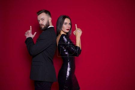 Beau couple en robe de luxe noire sur fond rouge. Saint-Valentin. Journée de la femme. 8 mars
