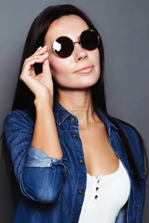 Portrait of a beautiful stylish woman in black glasses.