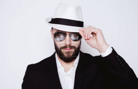 Elegant macho. Handsome young stylish bearded man in hat and sunglasses looking directly at the camera on a white background isolated.