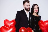 Beautiful young couple in love in black elegant costumes against a background of red balloons in the shape of a heart. Valentines day