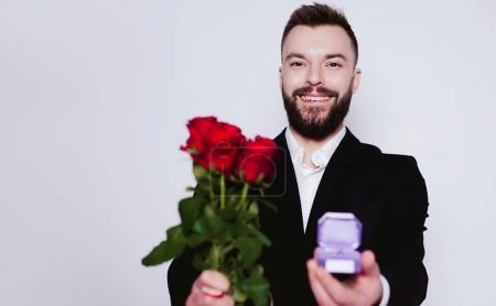 You will be my wife. Elegant beautiful smiling man with red roses and wedding ring in a box on a white background.