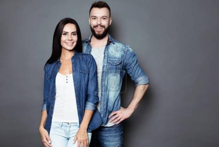 Beautiful and happy young couple in love or family in casual wear having fun and making fun of each other and posing on a gray background isolated.