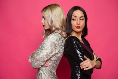 Quarrel between friends. Two angry and resentful girlfriend standing back to back on a pink background.