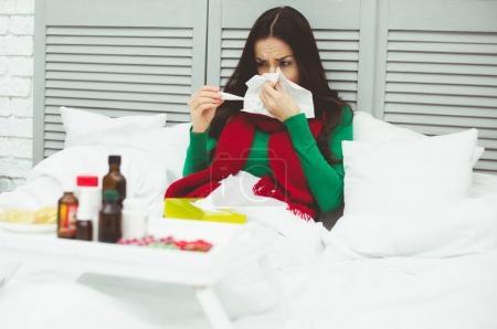 Photo pour Température corporelle très élevée. Une jeune femme malade dans une écharpe rouge mesure la température avec un thermomètre. Le concept de la santé et la maladie. - image libre de droit
