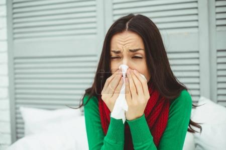 Close up portrait of a young sick woman with a runny nose in a red scarf lying on the bed at home and treated. The concept of health and disease.