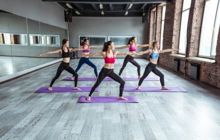 Photo pour Cours de yoga. Fitness, entraînement, sport, yoga et concept de personnes. Femmes souriantes faisant de l'exercice dans la salle de gym - image libre de droit