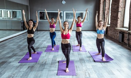 Yoga classes. Fitness, training, sport, yoga and people concept. Smiling women doing exercise in gym