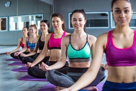 Photo pour Heureux groupe multiracial de jeunes belles femmes souriantes en vêtements de sport faisant des exercices de yoga en position lotus. Cours de yoga ou de fitness - image libre de droit