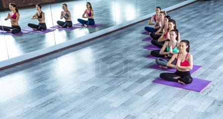 Photo for Multiracial Group of young women in sportswear doing yoga exercises with a coach or instructor. Class of yoga or fitness - Royalty Free Image