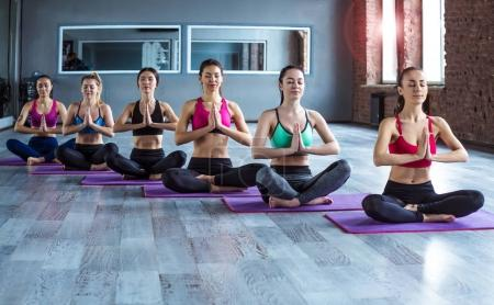 Multiracial Group of young women in sportswear doing yoga exercises with a coach or instructor. Class of yoga or fitness