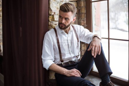 Photo for Fashion stylish confident portrair of handsome bearded guy on the big window looking away - Royalty Free Image