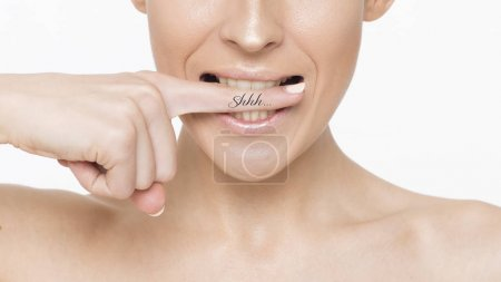 Close up Photo of a beautiful smiling female face with clean and fresh skin, the girl puts a finger to her lips.